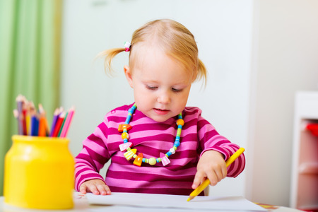 early education: Adorable happy toddler girl drawing with coloring pencils at home or daycare, perfect for early education context