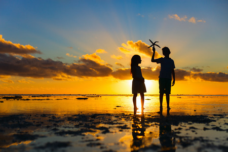 brothers: Silhouettes of kids brother and sister  holding starfish at tropical beach during sunset