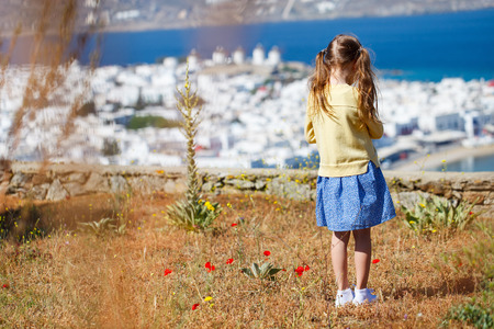 back view: Back view of little girl enjoying views of traditional white village on Mykonos island, Greece Stock Photo