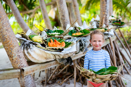 weaved: Little girl holding weaved plate with some local south pacific origin food served in giant shells Stock Photo