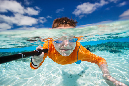 under: Cute teenage boy making selfie underwater in shallow turquoise water at tropical beach