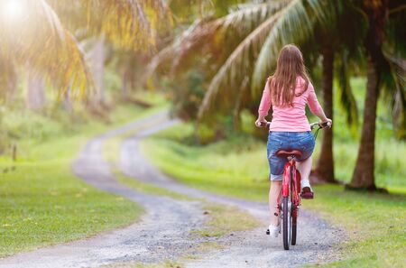 Back view of young woman biking at tropical settings having fun Stock Photo