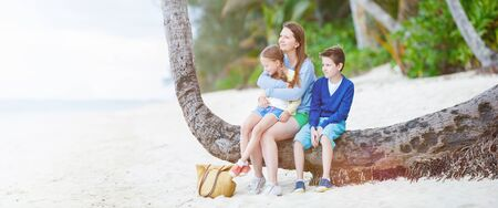 beach panorama: Mother and kids sitting on palm at perfect Caribbean beach