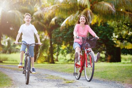 mama e hijo: Familia de madre e hijo en bicicleta con los ajustes tropicales se divierten juntos