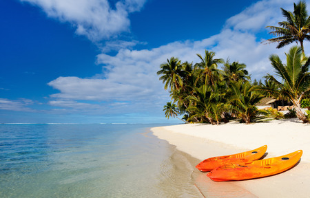 south pacific ocean: Two kayaks at beautiful tropical beach with palm trees, white sand, turquoise ocean water and blue sky at Cook Islands, South Pacific