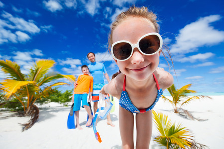 Girl and her with snorkeling equipment enjoying beach vacation