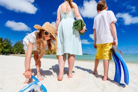 vacaciones en la playa: Familia alegre de la madre y los niños con la toalla y equipo de snorkel vacaciones disfrutando en la playa tropical