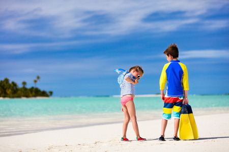 sun protection: Little kids in rash guards for sun protection with snorkeling equipment on tropical beach during summer vacation