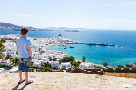back view: Back view of teenage tourist enjoying views of traditional white village on Mykonos island, Greece Stock Photo