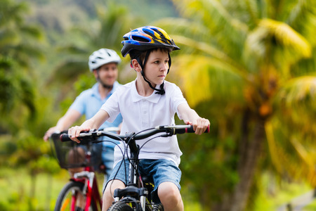 dad son: Family of father and son biking at tropical settings