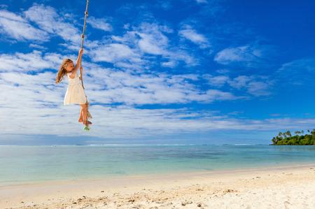 columpio: Niña que se divierte de balanceo en una cuerda en la playa de isla tropical