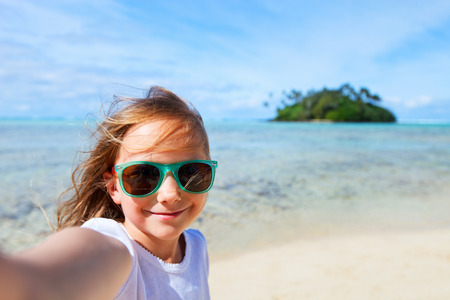 sun glasses: Adorable little girl making selfie in at tropical beach on Rarotonga island during summer vacation