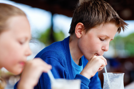 a straw: Kids brother and sister drinking milkshakes in outdoor cafe