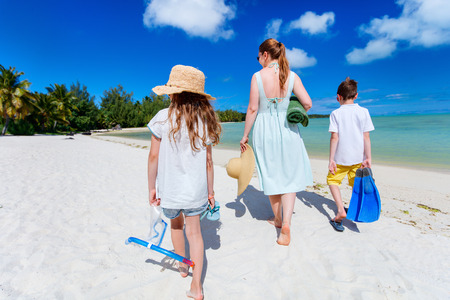 family vacation: Cheerful family of mother and kids with towel and snorkeling equipment enjoying vacation at tropical beach Stock Photo