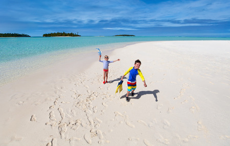 fun in the sun: Little kids in rash guards for sun protection with snorkeling equipment on tropical beach having fun during summer vacation