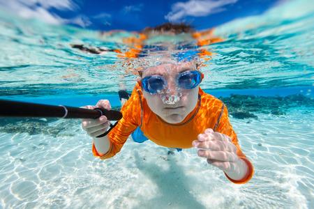kids swimming: Cute teenage boy making selfie underwater in shallow turquoise water at tropical beach