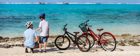 ecotourism: Father and kids enjoying sea view at tropical beach with their bikes parked nearby