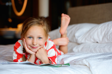 girl home: Adorable little girl at home resting on bed Stock Photo