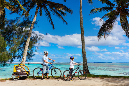 Family of father and kids biking at tropical beach
