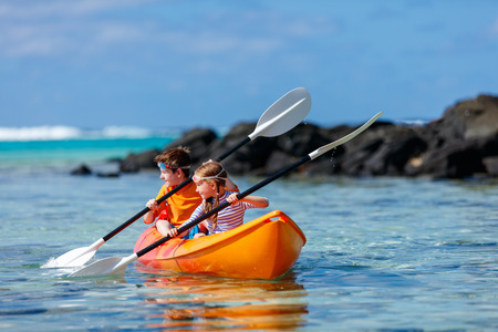 Kids enjoying paddling in colorful red kayak at tropical ocean water during summer vacation