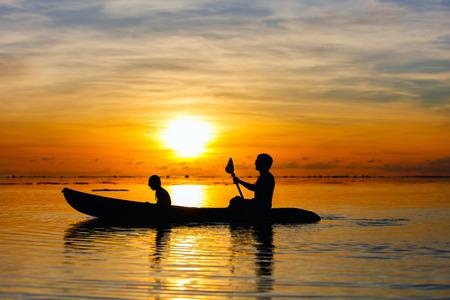 canoa: Siluetas de la familia de padre e hija remando en el océano tropical al atardecer