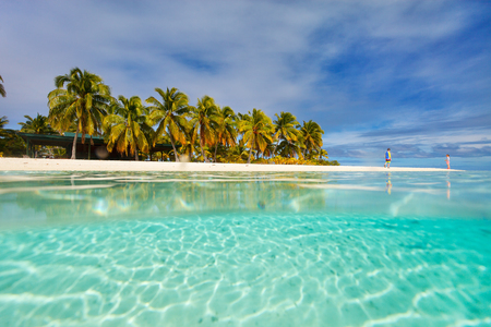 south pacific: Stunning tropical island with palm trees, white sand, turquoise ocean water and blue sky at Cook Islands, South Pacific