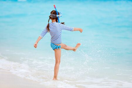 unrecognisable person: Back view of little girl with snorkeling equipment at beach during summer vacation