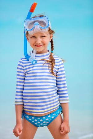 traje de baño: Niña adorable con equipo de snorkel en la playa durante las vacaciones de verano Foto de archivo