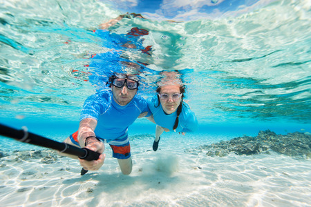 sea  scuba diving: Underwater photo of a couple snorkeling in ocean and making selfie with stick