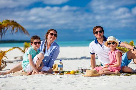 Glückliche schöne Familie auf einem tropischen Strand mit Picknick zusammen