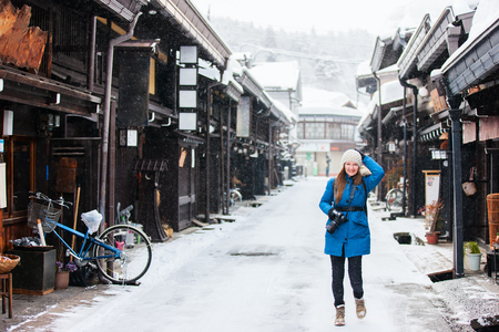 parka: Woman at old district of historical Takayama town in Japan on winter day