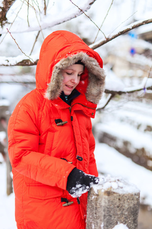 parka: Cute boy in a red parka down jacket outdoors on beautiful winter snow day Stock Photo