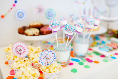 Colorful decoration of kids birthday party table with marshmallows and sweets