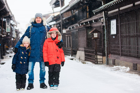 street kid: Family of father and kids at old district of historical Takayama town in Japan on winter day