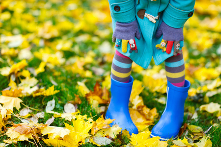Närbild på en liten tjej i färgglada kläder och blåa kängor utomhus vid vacker höstpark Stockfoto