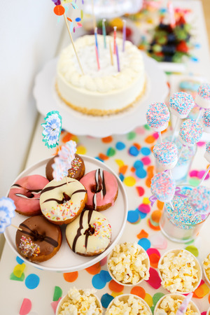 birthday party: Cake, candies, marshmallows, cakepops, fruits and other sweets on dessert table at kids birthday party Stock Photo
