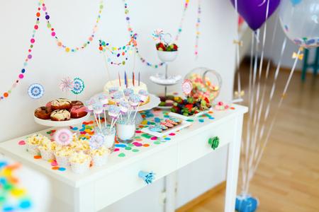 palomitas: La torta, dulces, bombones, cakepops, frutas y otros dulces en la mesa de postres en la fiesta de cumpleaños de los niños