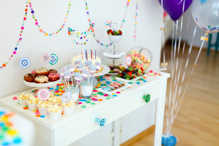 Cake, candies, marshmallows, cakepops, fruits and other sweets on dessert table at kids birthday party Archivio Fotografico
