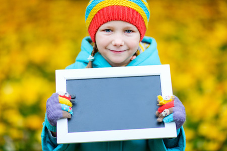 kids outside: Adorable little girl holding empty blackboard at beautiful autumn park