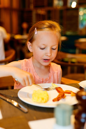 bacon portrait: Adorable little girl eating breakfast in restaurant Stock Photo