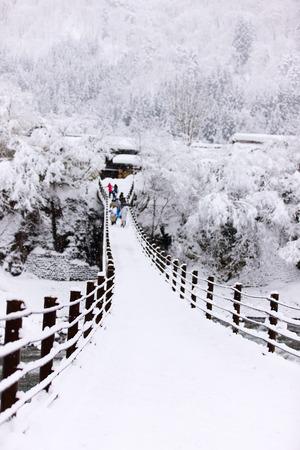 shirakawago: People crossing the bridge over Shogawa river at historic Japanese village Shirakawa-go at winter, one of Japans