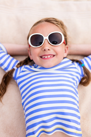 girl lying: Adorable little girl lying on a beach towel during summer vacation