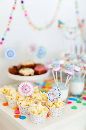 kids birthday party: Colorful decoration of kids birthday party table with popcorn and sweets