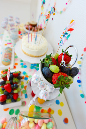 kids birthday party: Cake, candies, marshmallows, cakepops, fruits and other sweets on dessert table at kids birthday party Stock Photo