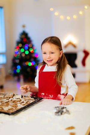 baking christmas cookies: Little girl baking Christmas cookies at home