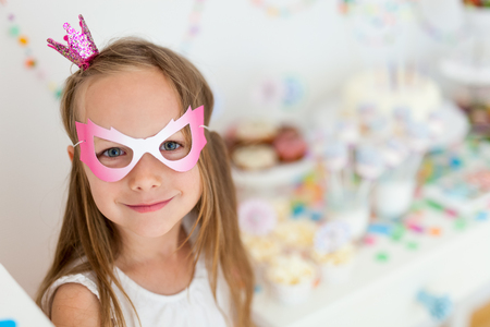 Adorable little girl with princess crown at kids birthday party 스톡 콘텐츠