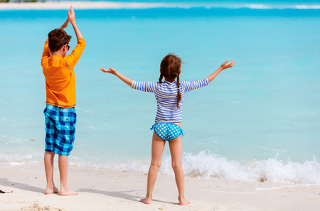 sun protection: Little kids in rash guards for sun protection on tropical beach during summer vacation