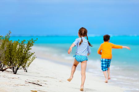 people jumping: Niños que se divierten en la playa tropical durante las vacaciones de verano