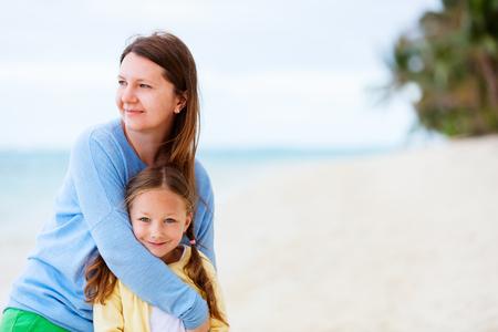 mama e hija: Hermosa madre y su pequeña hija adorable en la playa