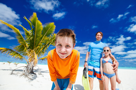 traje de baño: Muchacho y su familia con el equipo de snorkel disfrutando de vacaciones en la playa
